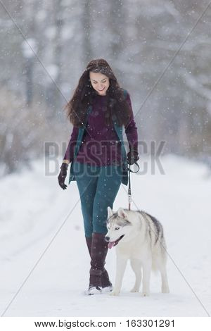 Stylish Caucasian Brunette Woman in Country Style Airing Her Husky Dog in Winter Snowy Forest Outside.Vertical Image