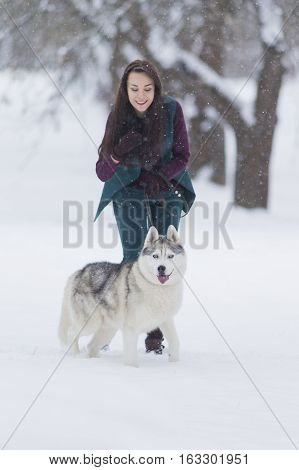 Pets Concepts and Ideas. Happy and Smiling Caucasian Brunette Woman Playing with Husky Dog Outdoors in Park. Vertical Image