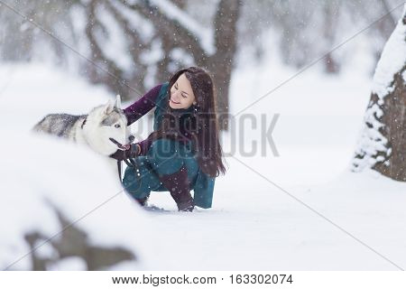 Pets Concepts and Ideas. Happy and Smiling Caucasian Brunette Woman Playing with Husky Dog Outdoors in Park. Horizontal Image