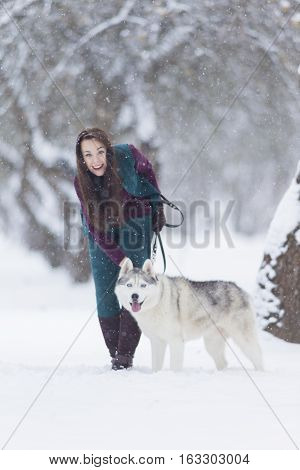 Happy Smiling Caucasian Brunette Woman and Her Husky Dog. Playing Outdoors in Winter White Forest. Vertical Orientation