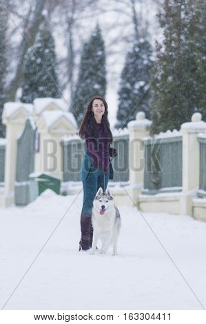 Woman and Her Lovely Husky Dog Taking a Stroll Together Outside.Vertical Image Orientation