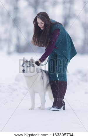Lovely Couple. Portrait of Smiling and Happy Caucasian Woman Airing Her Husky Dog Outdoors. Vertical Image