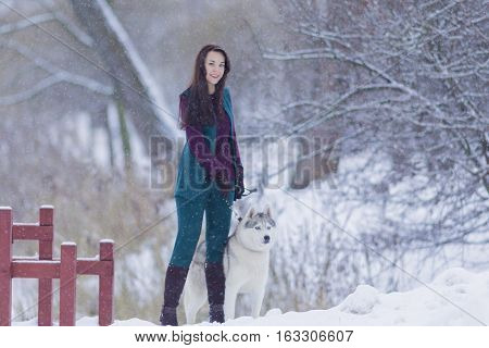 Pretty Tranquil Caucasian Brunette With Her Husky Dog during a Stroll in Winter.Horizontal Image