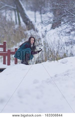 Pretty Tranquil Caucasian Brunette With Her Husky Dog during a Stroll in Winter. Vertical Image