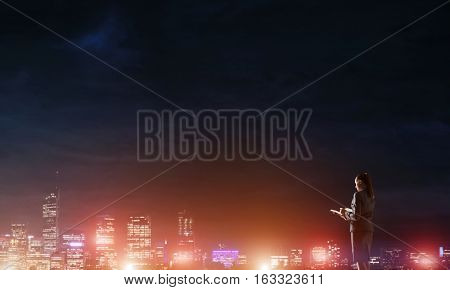 Rear view of elegant businesswoman writing in diary against night city background