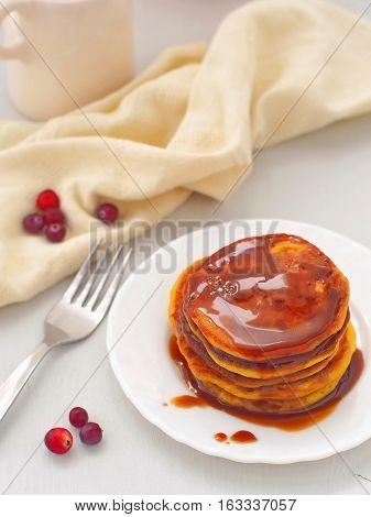Pumpkin pancakes with caramel sauce and cranberries. Fresh homemade flapjacks. Top view.