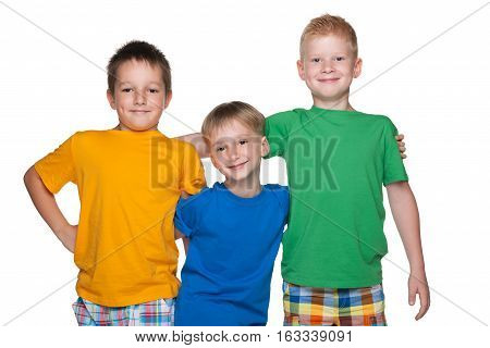 Three happy young boys are standing together against the white background