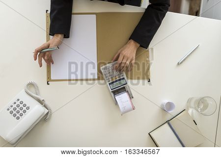 Overhead view of businessperson using a calculator on a desk with blank paper.