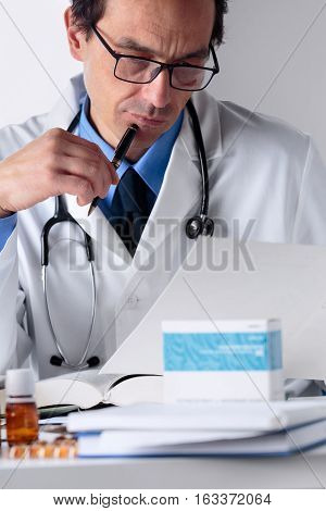 Male Doctor Working At His Office Desktop, Examining Medical Reports