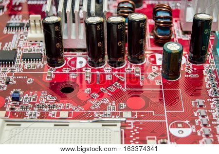 red computer motherboard with microcircuit close up