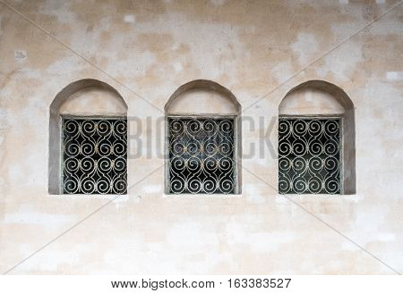 Three old deep windows in row with iron grating. Old vintage building exterior with stone surface.