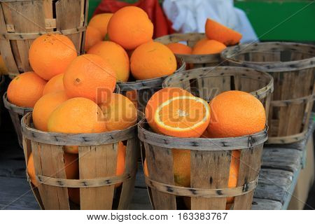 Wood baskets filled with ripe oranges, some cut in half to show customers how fresh and juicy they are before buying.
