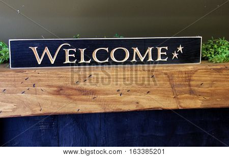 Large, colorful wood sign that has the word 'welcome' carved on the face of it