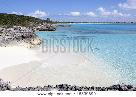 Crystal sea water washes small beach on uninhabited Half Moon Cay island (The Bahamas).