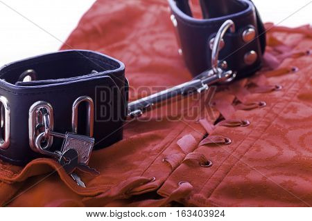 Sexy leather hand cuffs on a red satin corset. Symbolising bondage and sexual role play.