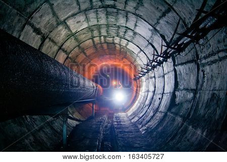 Diggers in round underground tunnel of heating duct with rusty tubes