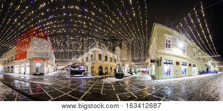 BRASOV ROMANIA - 15 DECEMBER 2016: Panoramic night view of Republic Street decorated for winter hollidays with Christmas lights in Brasov old city center Romania
