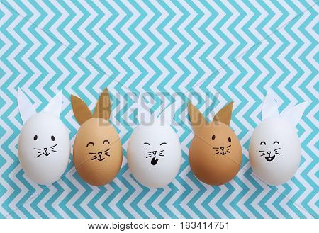 Brown and white Easter bunny eggs on a blue chevron striped background
