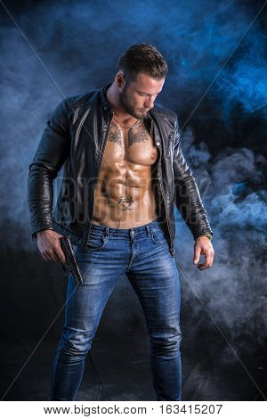 Handsome man wearing leather jacket on naked muscular torso holding hand gun, on dark smoky background, looking straight.