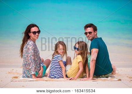 Young family on vacation on tropical beach during summer vacation