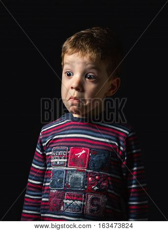Portrait of confused boy with a doubt face standing over black background
