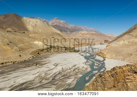 Glacier river flowing through mountain wasteland. Tourist limited access area of Mustang in Nepal.
