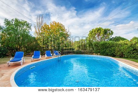 Swimming pool garden in summer with sun beds for relaxing. With clean water.