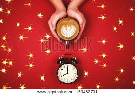 Two hands holding a cup of fresh cappuccino with latte art and alarm clock on red background. Time for coffee concept. Sparkling stars on backdrop. Flat lay Style.