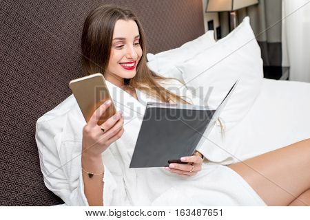 Young woman in bathrobe lying on the bed in the hotel room. Calling with mobile phone to the concierge service