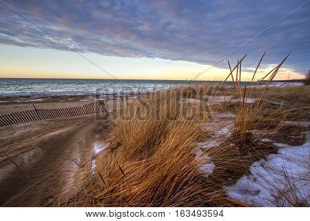 Winter Sunset On The Great Lakes Coast.  Sunset horizon on the windswept shore of the Lake Huron coast in Port Austin, Michigan.