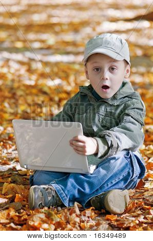 surprised boy with laptop in forest