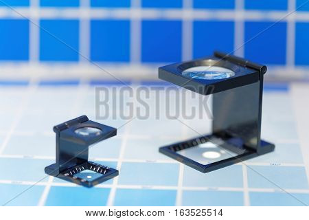 Two magnifier or printer's loupe sits on a cyan test sheet in a pre-press workshop. Very short depth of focus