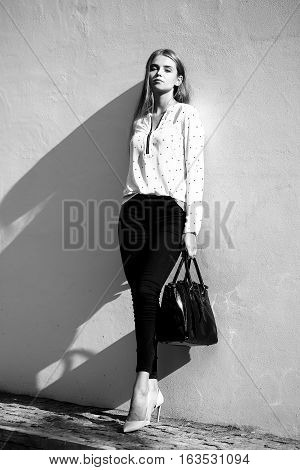 Pretty cute business woman or girl with long hair in pants fashion bag and blouse on high hells posing outdoor on wall background black and white