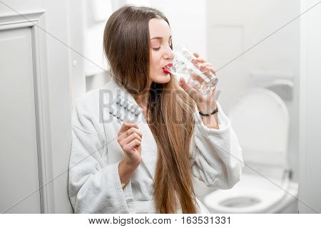 Woman in bathrobe taking pills and drinking water in the bathroom
