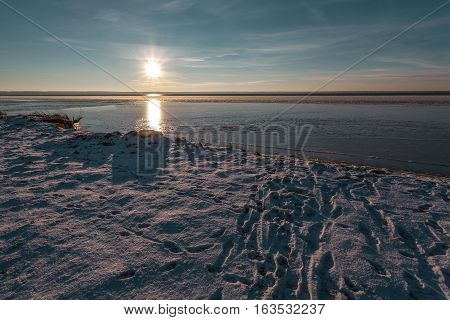 Human traces on snow conduct on thin ice of the lake on a winter decline.