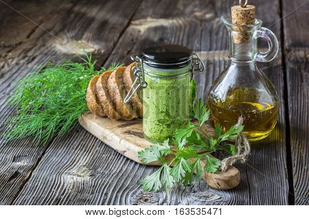 Green oil with herbs. creamy homemade butter bar with fresh seasonal herbs garden young green garlic, dill, parsley, cilantro on a cutting board with olive tree on a dark wooden background.