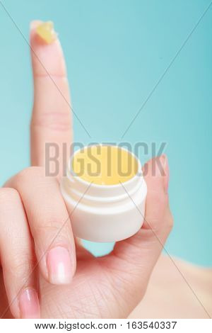 Woman Hand About To Apply Yellow Cream.