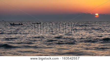 Fishing boats on waves of the Indian Ocean against the background of the sunset. The sun hides in clouds.