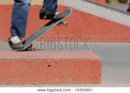 skateboard feet doing tail grind off ramp at skatepark
