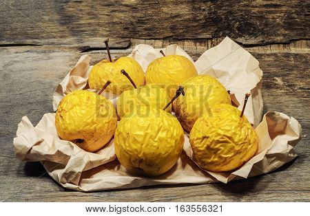 shriveled yellow apples on crumpled paper. Wooden background