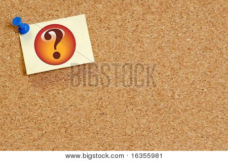question mark on note pinned on cork board background