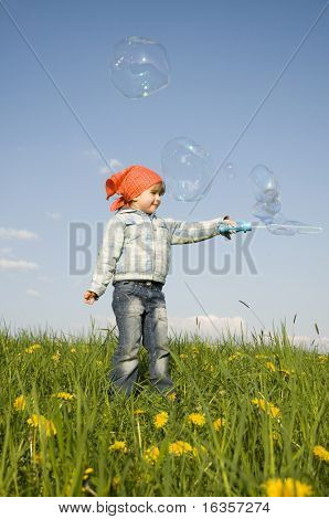 Little girl playing on spring meadow