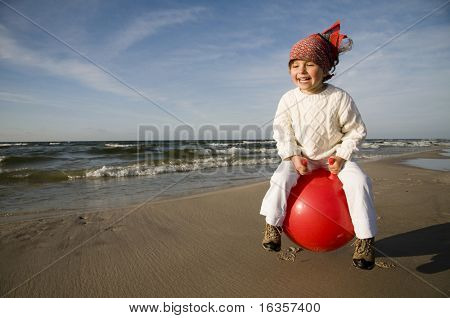 Young laughing girl bouncing on a red space hopper