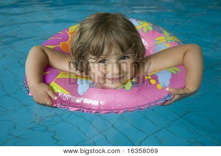 Little girl with inner tube floating on swimming pool