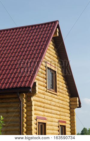 Top of country wooden house with red roof and windows closeup