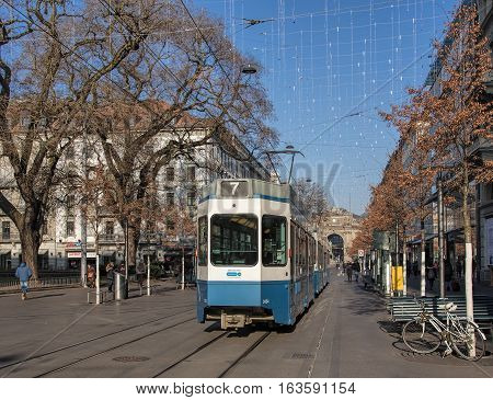 Zurich, Switzerland - 1 January, 2017: a tram passing along Bahnhofstrasse street, people on the street, lamps of the Christmas illumination above it. Bahnhofstrasse is Zurich's main downtown street.