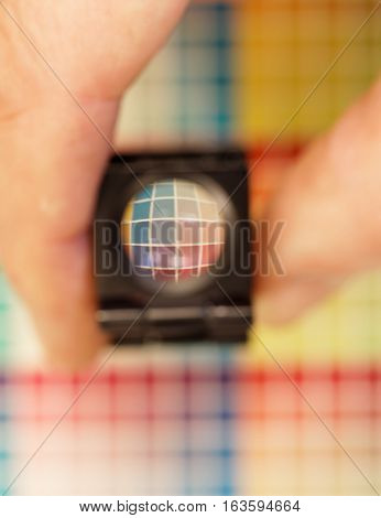 Hand holding a magnifyer or loupe above a colorful test print with color shades in cyan blue magenta red green orange and yellow. Short depth of focus