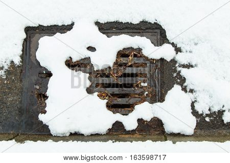 Snow clogged street drain with small stream of water