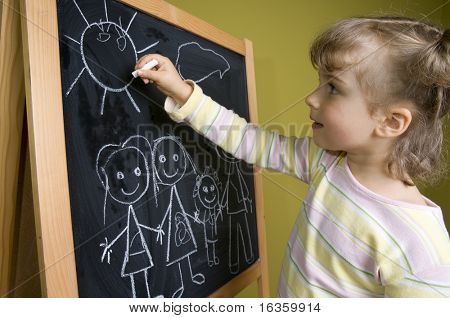 Little girl  drawing family on blackboard; education