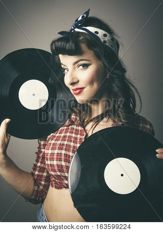 Gorgeous retro pin up girl with her hair tied up in a polka dot bandanna and hair in bangs posing with LP vinyl records in her hands smiling at the camera